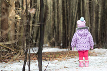 toddler girl standing in the snow