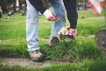 laying flowers at a grave site