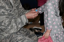 an Air Force father putting on an armband on his toddler daughter at a carnival, a solider spending time with his family before his next deployment