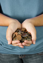A young person holding out a hand full of coins