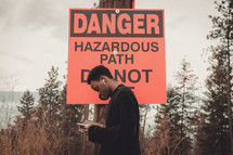 young man in front of a Dangerous Hazardous Path sign