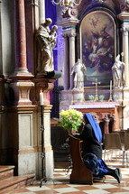 Nun at prayer before a statue of the Mother Mary and baby Jesus in a Catholic Cathedral.