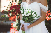 torso of a bride holding white tulips