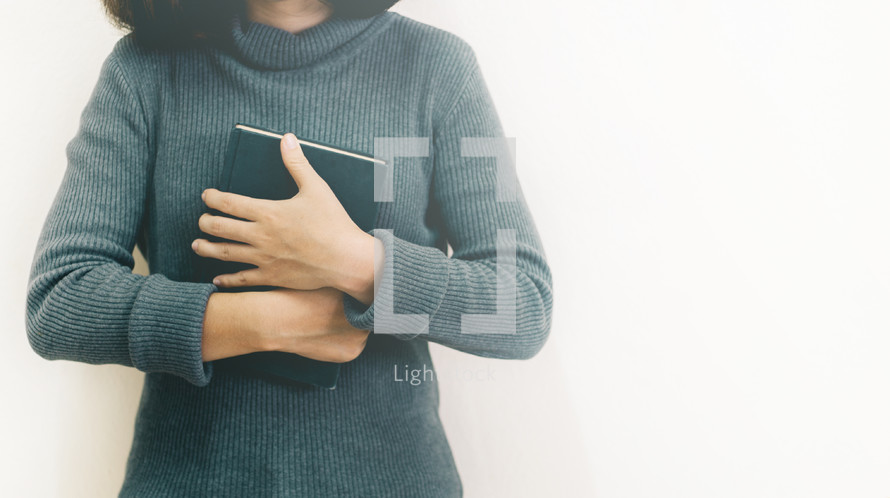 a woman holding a Bible close to her chest