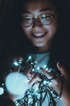 a woman holding a string of lights