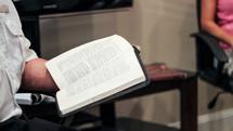 a man reading scripture at a Bible study
