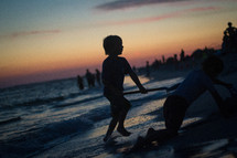 Kid playing on the beach at sunset