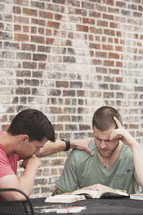 men reading a Bible and praying at a Bible study
