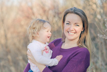 a mother holding her toddler daughter
