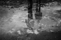 reflection of children in a puddle