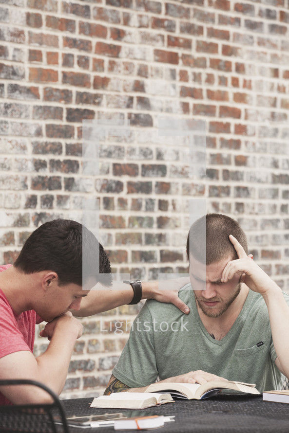 men reading a Bible and praying at a Bible study