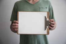 man holding a blank piece of paper on a clipboard
