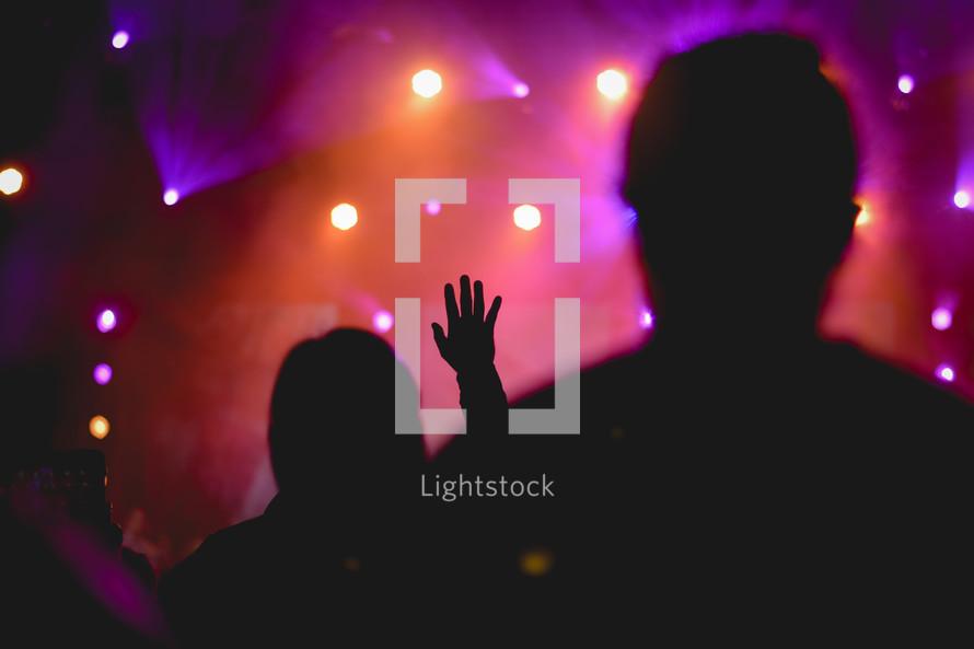 silhouette of a raised hand under spotlights