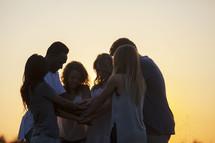 prayer circle outdoors at sunset