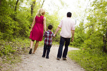 Back view of mother, father and son walking dow a wooded path