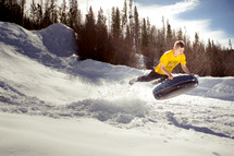 s man tubing in the snow