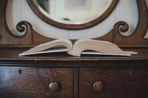 open Bible on a dresser