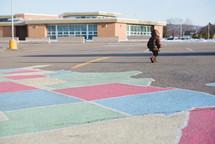 a child walking across a school parking lot