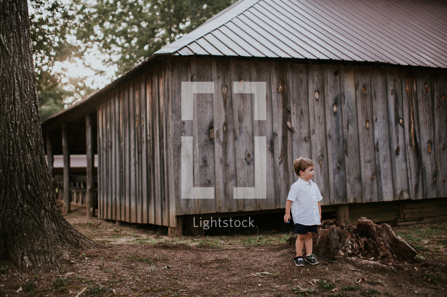 toddler boy in front of a cabin