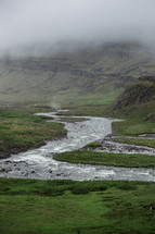 flowing stream in a foggy landscape