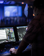 A sound technician in a sound booth during a church service.