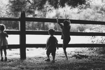 Children climbing on a wooden fence.