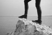 feet standing on a rock by water