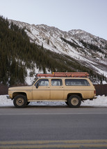 vintage suburban parked in front of a snow covered mountain