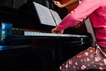 a girl child in pajamas playing a piano