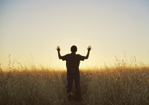 silhouette of a young man with raised hands standing in a field