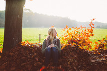 woman sitting in a pile of fall leaves outdoors
