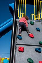 toddler climbing a climbing wall on a playground