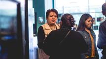 women talking in a church lobby