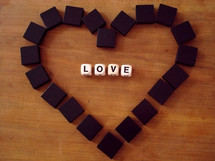 "Letter blocks spelling out ""love"" surrounded by a heart of blocks."