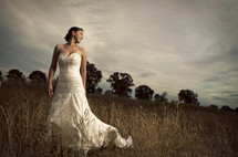 bride standing in a field - tree background - cloudy sky