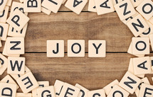 scrabble pieces and the word joy