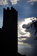 clouds peeking behind a castle tower