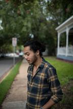 a man standing on a neighborhood sidewalk waiting