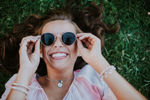 young woman with sunglasses lying in grass