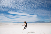 a woman leaping up over sand in a desert