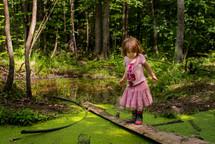 little girl exploring a pond