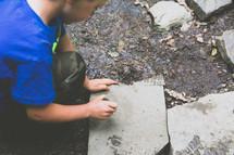 boy child looking under rocks