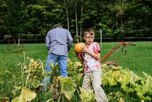 grandfather and grandson picking pumpkins in a garden