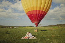 A couple kissing on a blanket with a hot air balloon in the background