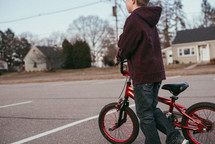 A boy riding a bike in a parking lot on a spring day.