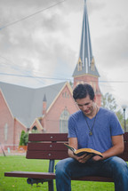 a man sitting on a bench reading a Bible and a church in the background