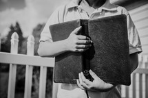 a boy holding a Bible close to his chest