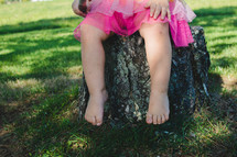 legs of a toddler girl sitting on a stump