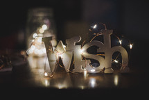 Fairy lights surrounding the word Wish that is sitting on a table.