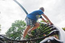 a boy child climbing on playground equipment